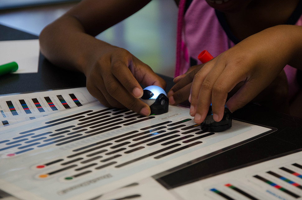 Children play with robots that follow color patterns during a Perot Museum Tech truck stop at the Park in the Woods Rec Center in Dallas.  [ Photo by Hannah Ridings ]