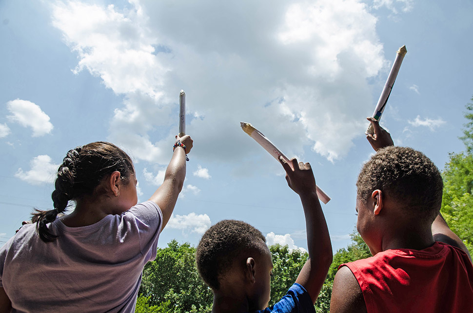 Children talk about how high their rockets are going to fly in the air during a Perot Museum Tech truck stop.  [ Photo by Hannah Ridings ]