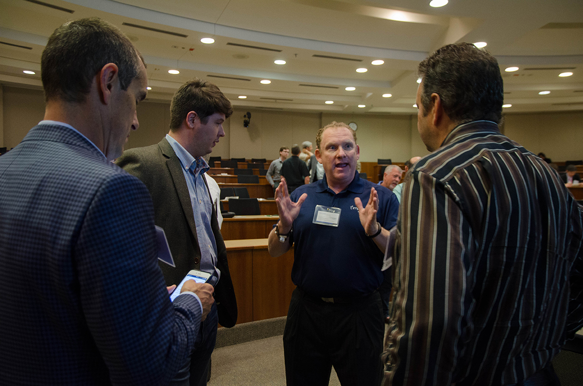 Tad Molntosh (middle) talks business with Moderator Bob Gessel (right) during networking hour at Tech Titans. Photo by Hannah Ridings.
