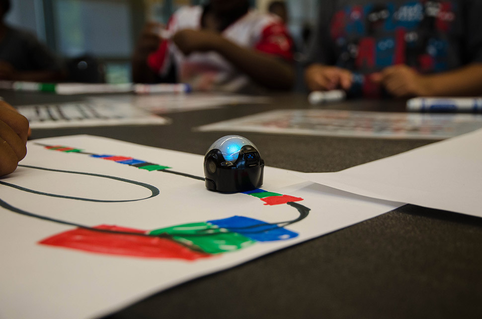 A robot follows color patterns at the Park in the Woods Rec Center during a Perot Museum Tech truck stop.  [ Photo by Hannah Ridings ]