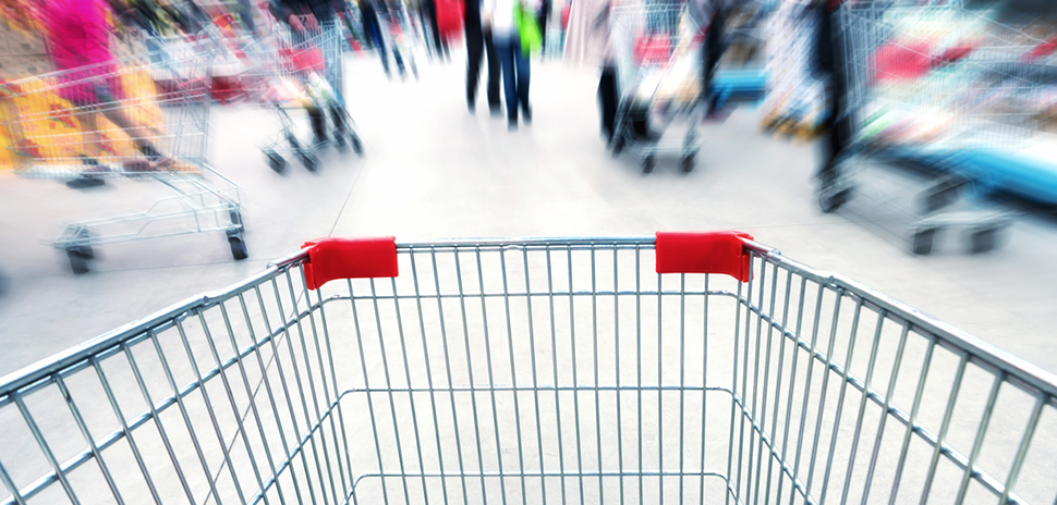 Cart in supermarket or mall full of crowded people. Blur motion.