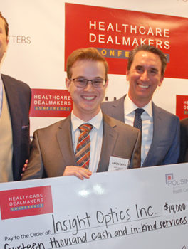 Aaron Enton of Insight Optics holds the winner's check at the Health Wildcatters Pitch